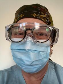 Esther takes a selfie of herself wearing goggles over glasses, a blue mask, and scrubs.