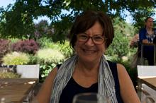 Janet Ramsey smailes, holding a coffee cup in front of a shaded garden