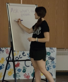 "Peace Camp Leader writing ""Ask what the problem is"" on a large sketch pad."