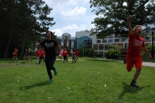 Peace Camp Volunteet Leader running with Peace Campers outside on the grass
