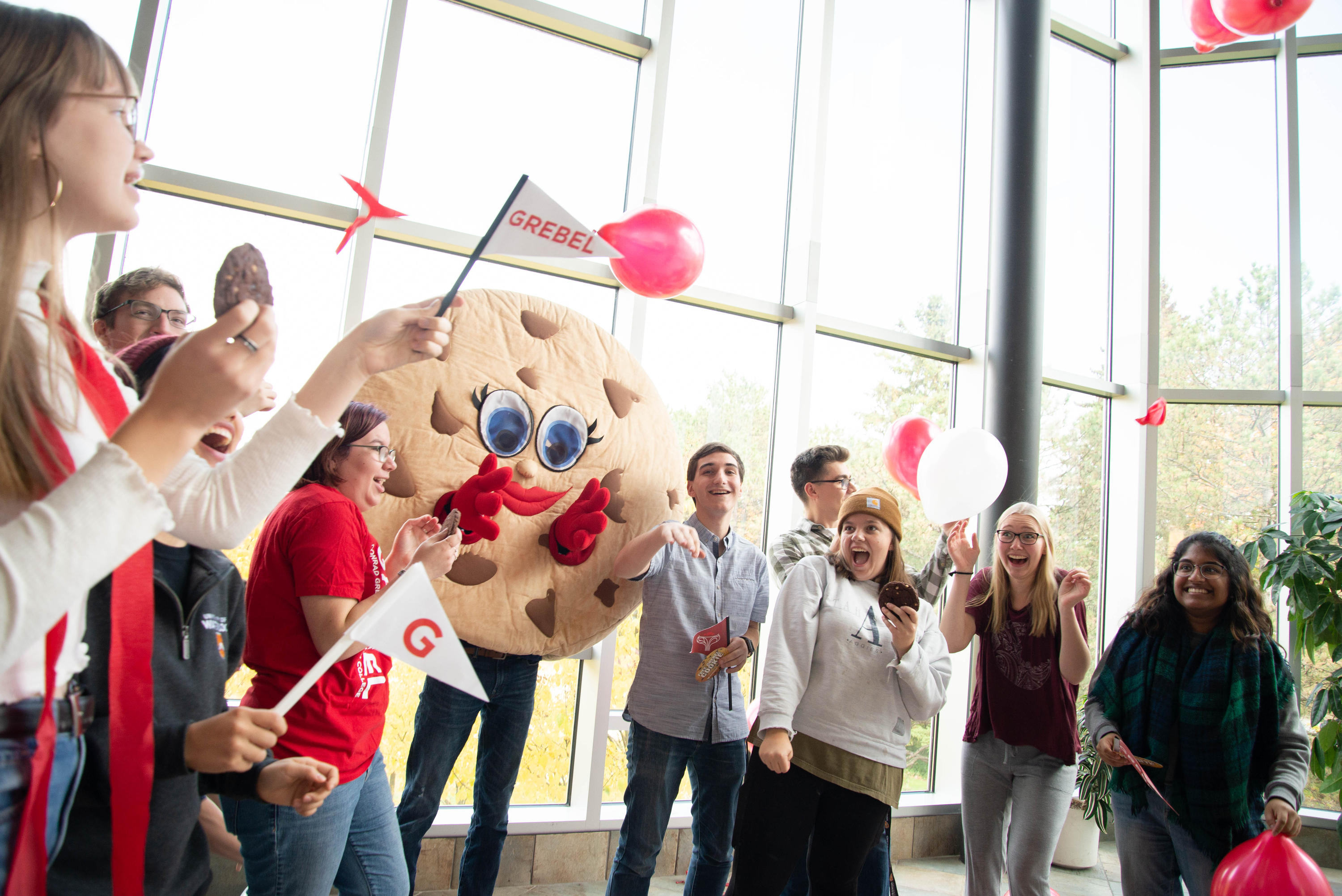 Picture of grebelites who are holding cookies and are dancing with the cookie mascot