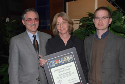 Ruth Teichroeb receiving the Distinguished Alumni Service Award from Henry Paetkau and another person