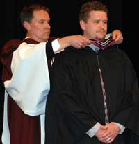 Jim hooding Andrew in the convocation