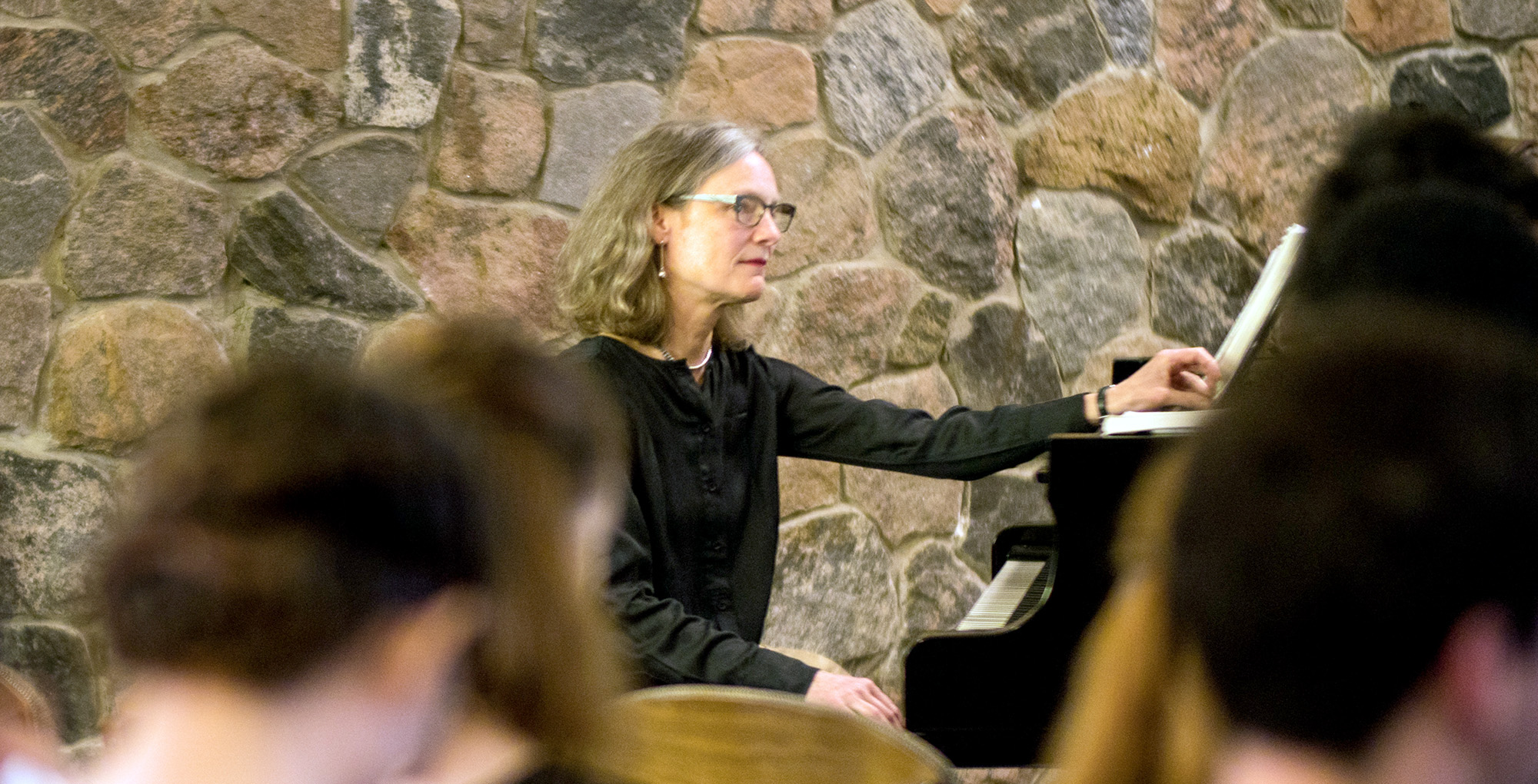 Catherine Robertson sits at a piano in a full Grebel chapel.