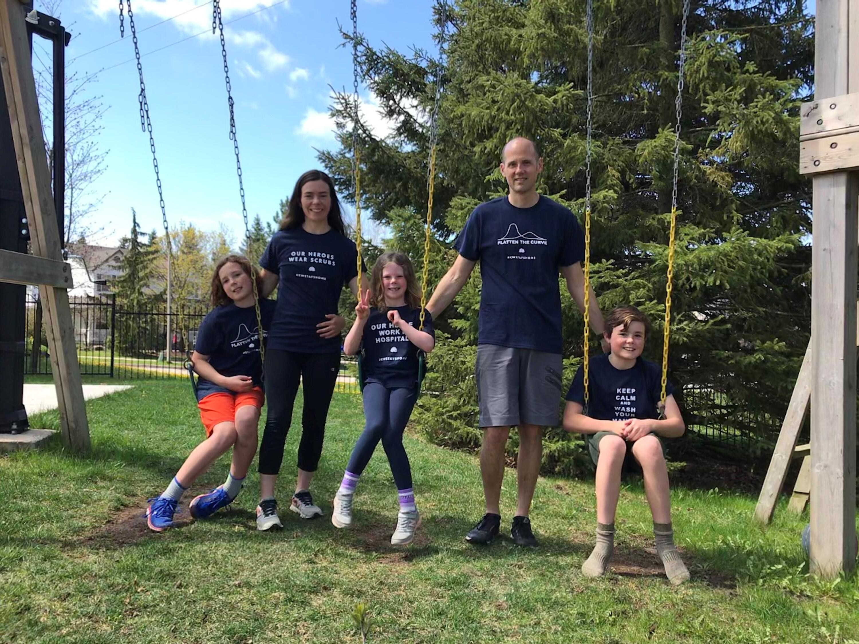 Jay Green stands at a swing set with his wife and two kids. They wear black shirts that promote flattening the COVID-19 curve.