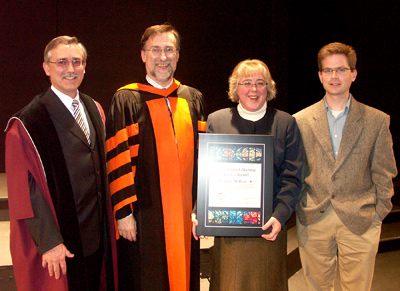 Lynn McRuer receiving the Distinguished Alumni Service Award from Henry Paetkau, Kenneth Hull, and another person