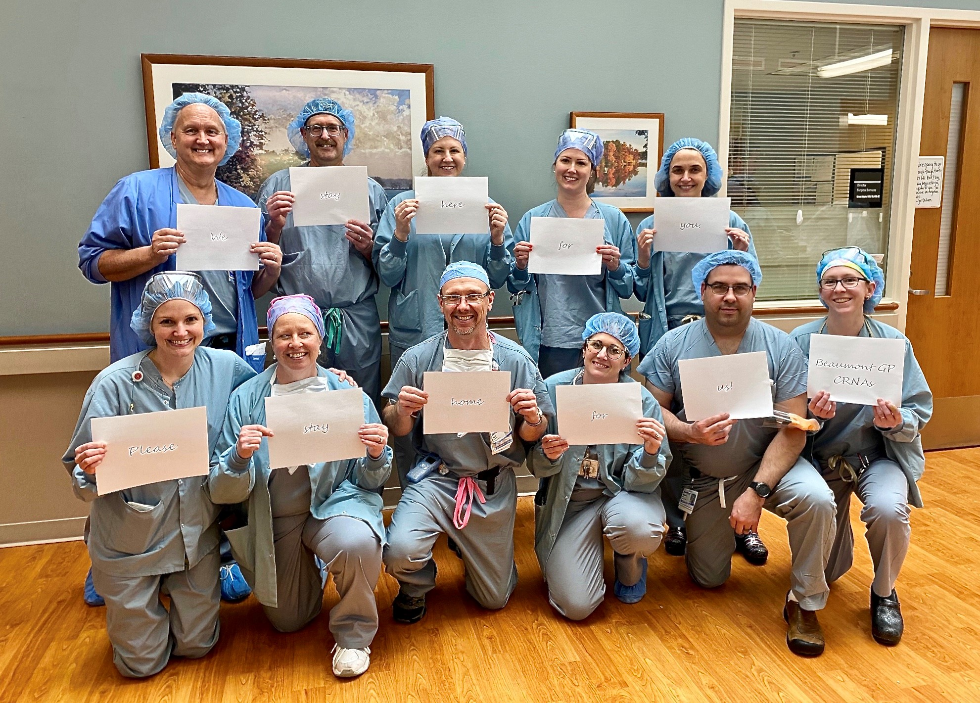"Mike stands in a group picture with the health team, each dressed in scrubs holding up paper that says ""we stay here for you. Pleas stay home for us."""