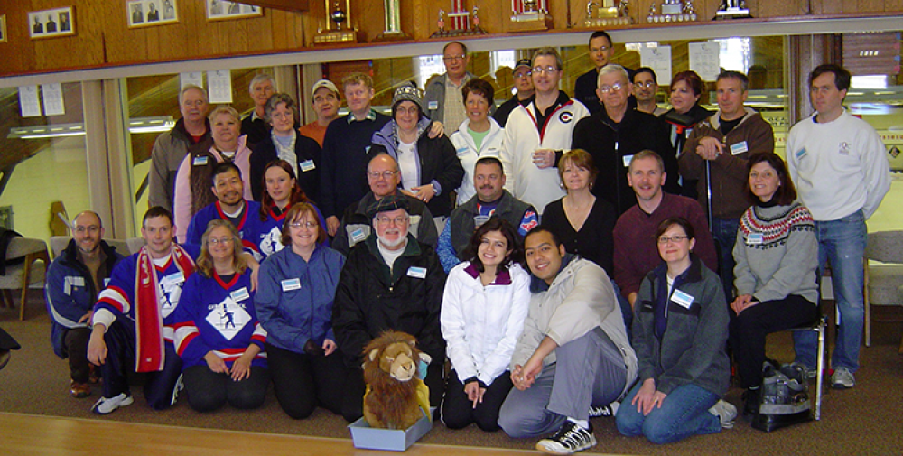 Group photo of bonspiel curlers with stuffed lion.