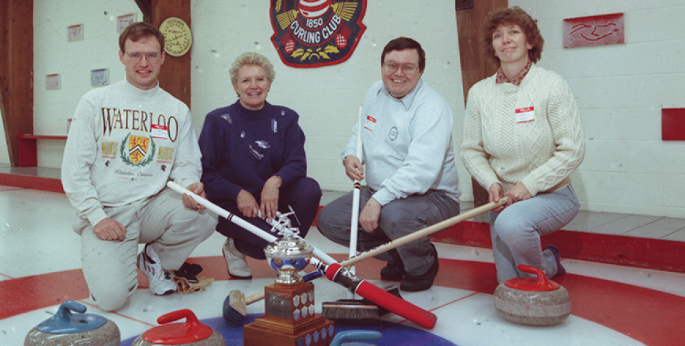Curlers kneeling at button with trophy and brooms.