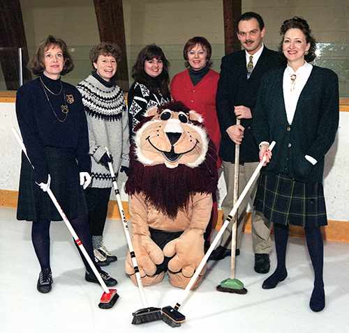 Curlers with brooms and stuffed lion.