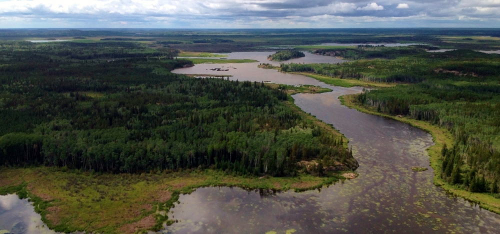 View from a helicopter of a series of connected lakes and wetlands, surrounded by boreal forest, and stretching into the dist