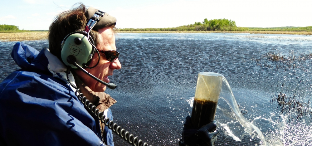 Prof. Roland Hall is wearing helicopter head-phones while collecting sediment from a lake.
