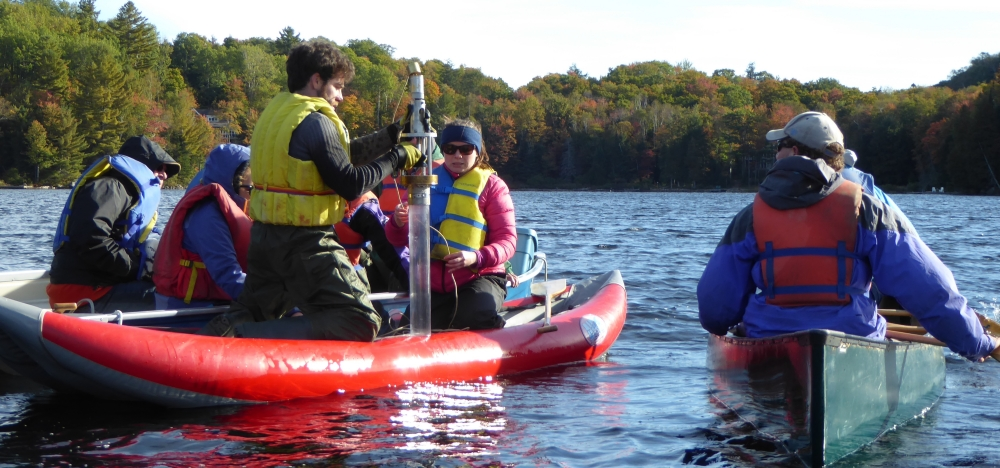 People in a canoe and boat watch as a student uses a sediment coring device off of an inflatable raft in a lake.