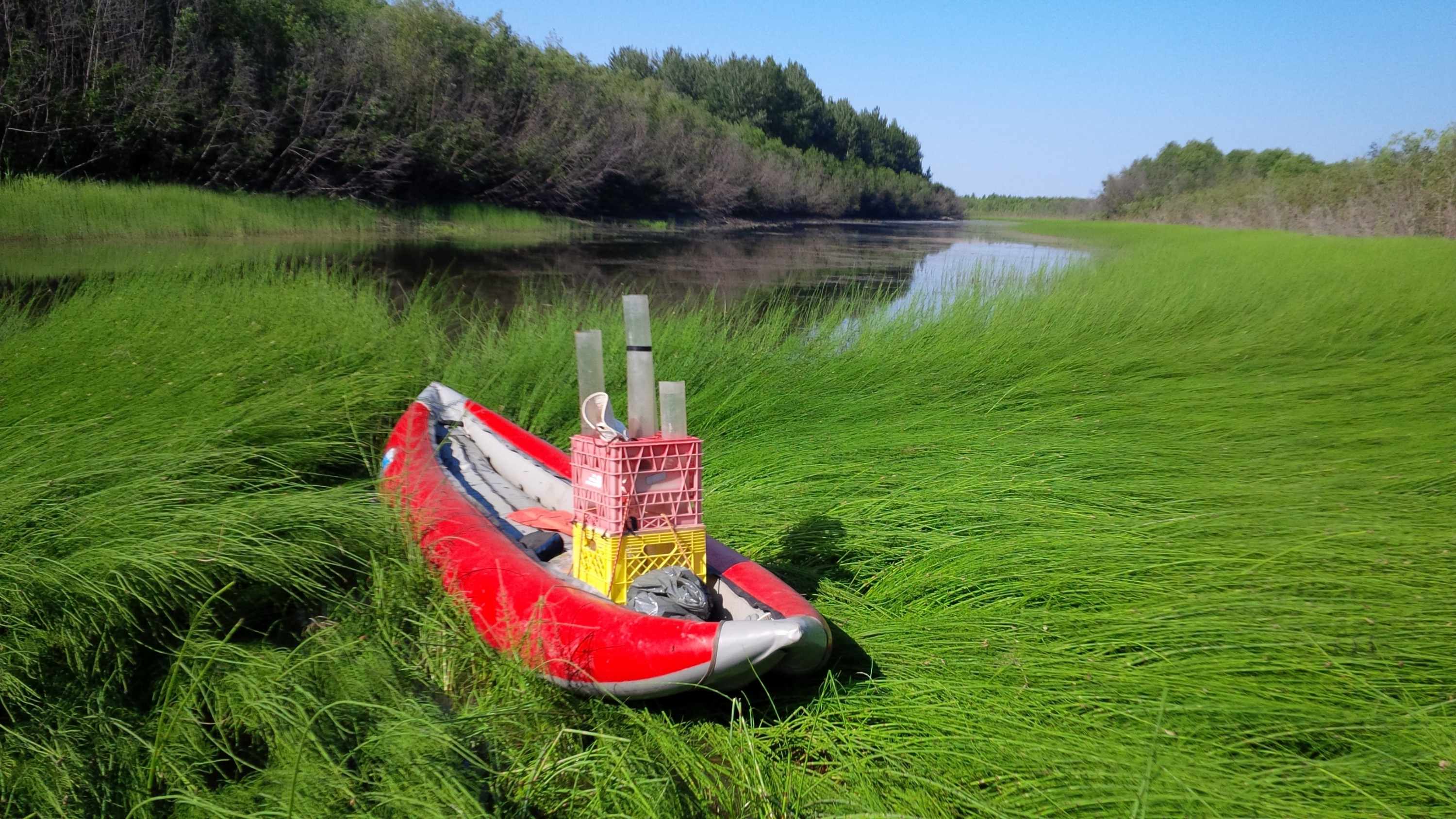 A red boat sits on green grass next to a small lake