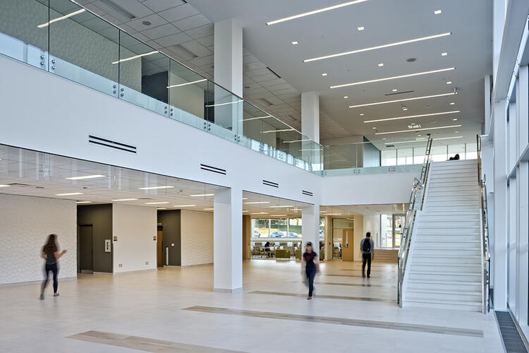 Applied health sciences building foyer with white walls, staircase and floor to ceiling windows.