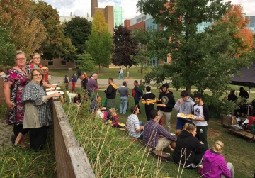 Faculty, staff, students and family enjoying corn roast on BMH Green.