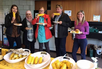 Faculty and students eating corn.