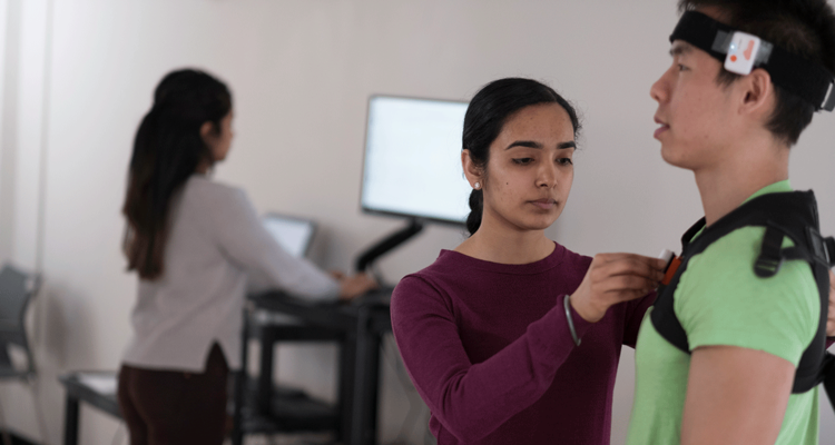 Co-op student connects wearable health monitoring devices on a client.