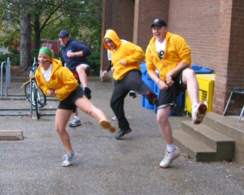 Three students in yellow hoodies and one in a blue sweater doing a dance move
