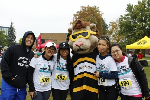 Five racers standing with King Warrior mascot
