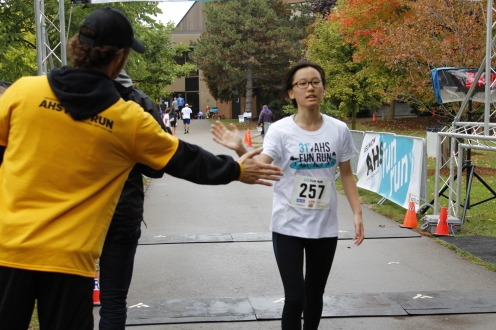 A boy crossing the finish line and giving a volunteer a high five