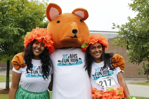 Two runners with AHSSIE the mascot