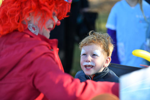 Dotsy The Clown face painting a child