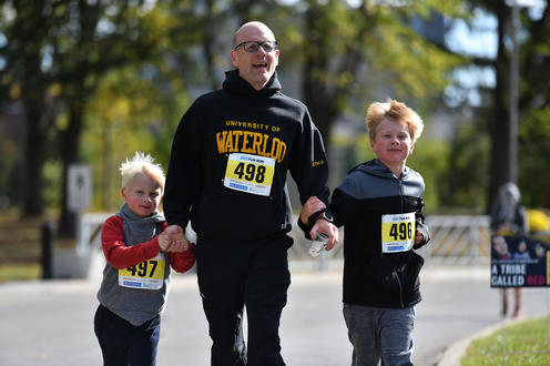One father and two children running