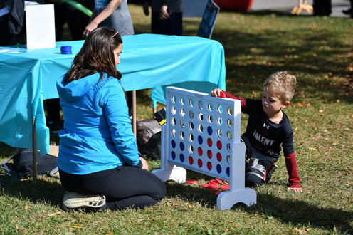 Child playing Connect4 with Fun Run volunteer