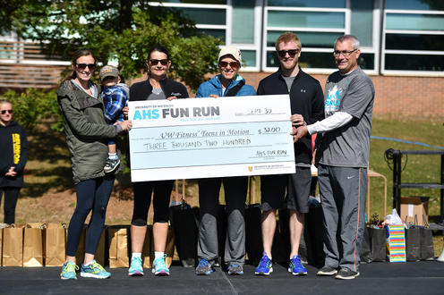 UW Fitness receiving a cheque for 00 on stage for Teens In Motion