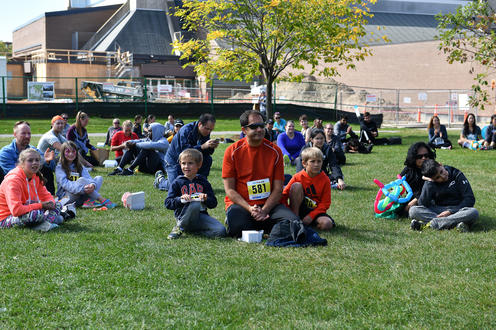 Fun Run participants sitting on the grass smiling