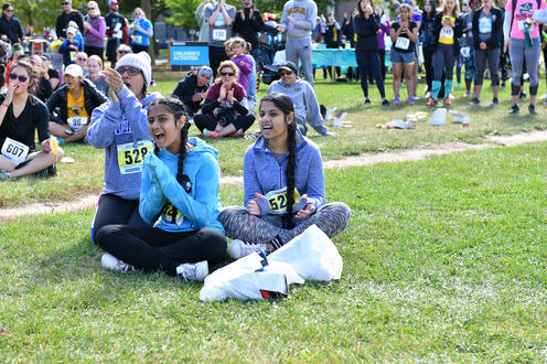 Fun Run participants sitting on the grass laughing