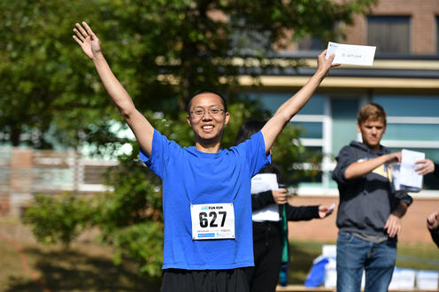 Fun Run prize winner smiling with arms up