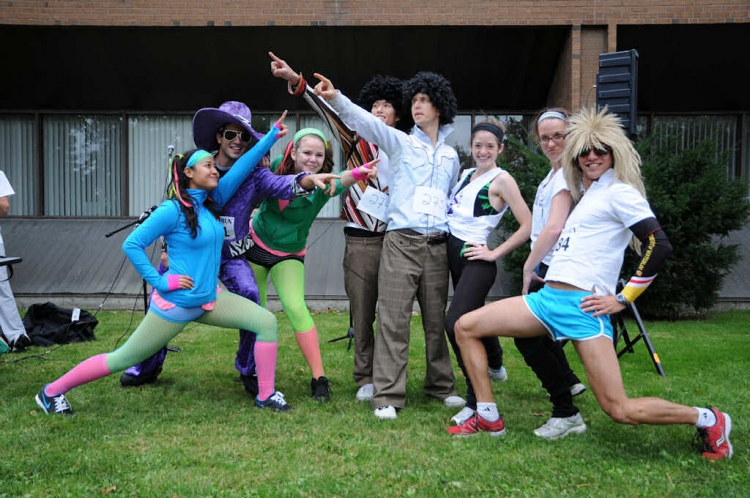 Eight people in costumes posing