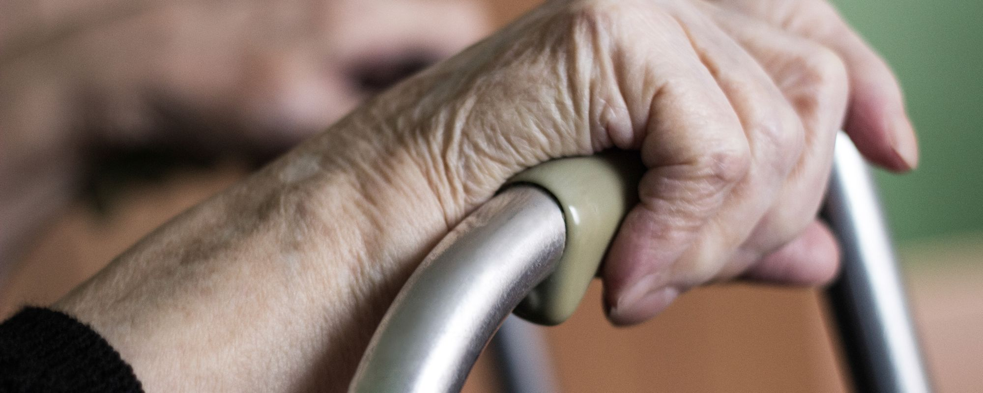Older person's hand gripping a walker.