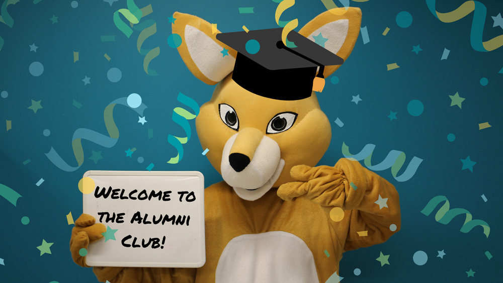 Mascot AHSSIE in graduation cap holding Welcome to the Alumni Club sign.