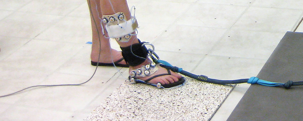 Lab photo of subject's foot wearing flip flop with video markers attached.