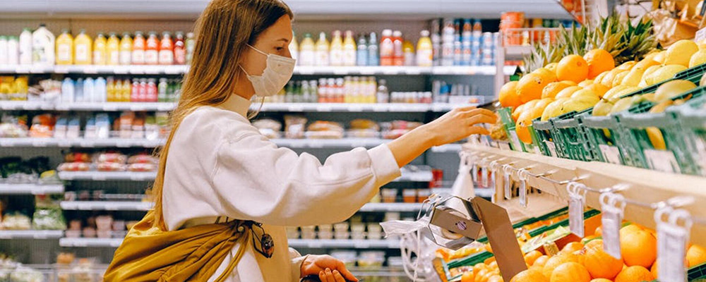 Woman with mask shopping in the produce aisle.