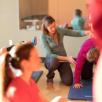 Trainer guides adult in performing exercise.