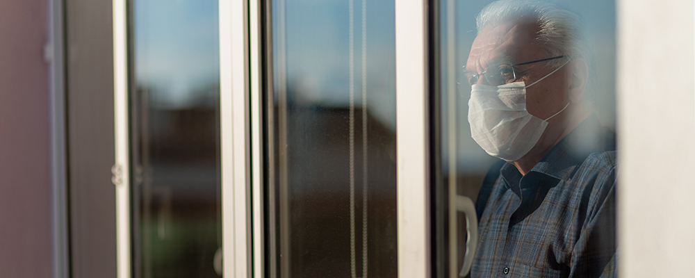 Elderly man with mask looking out of window