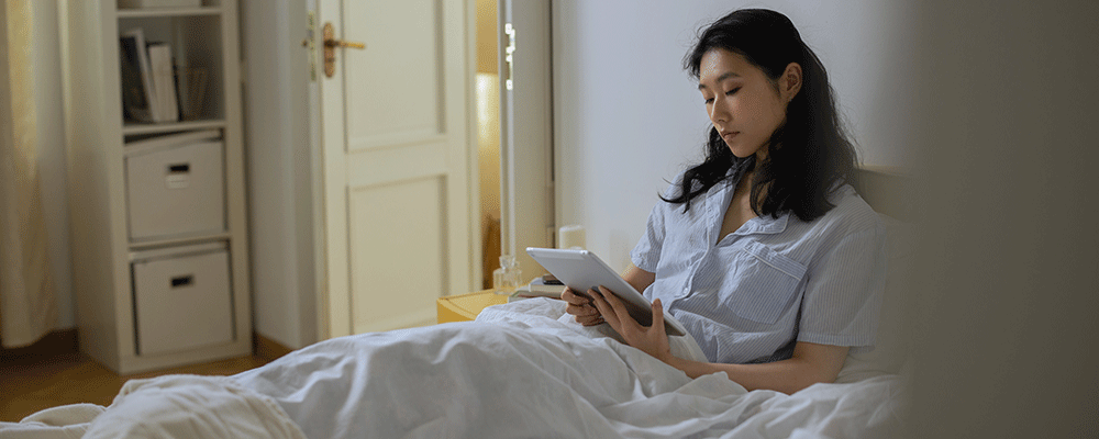 Women in bed holding iPad