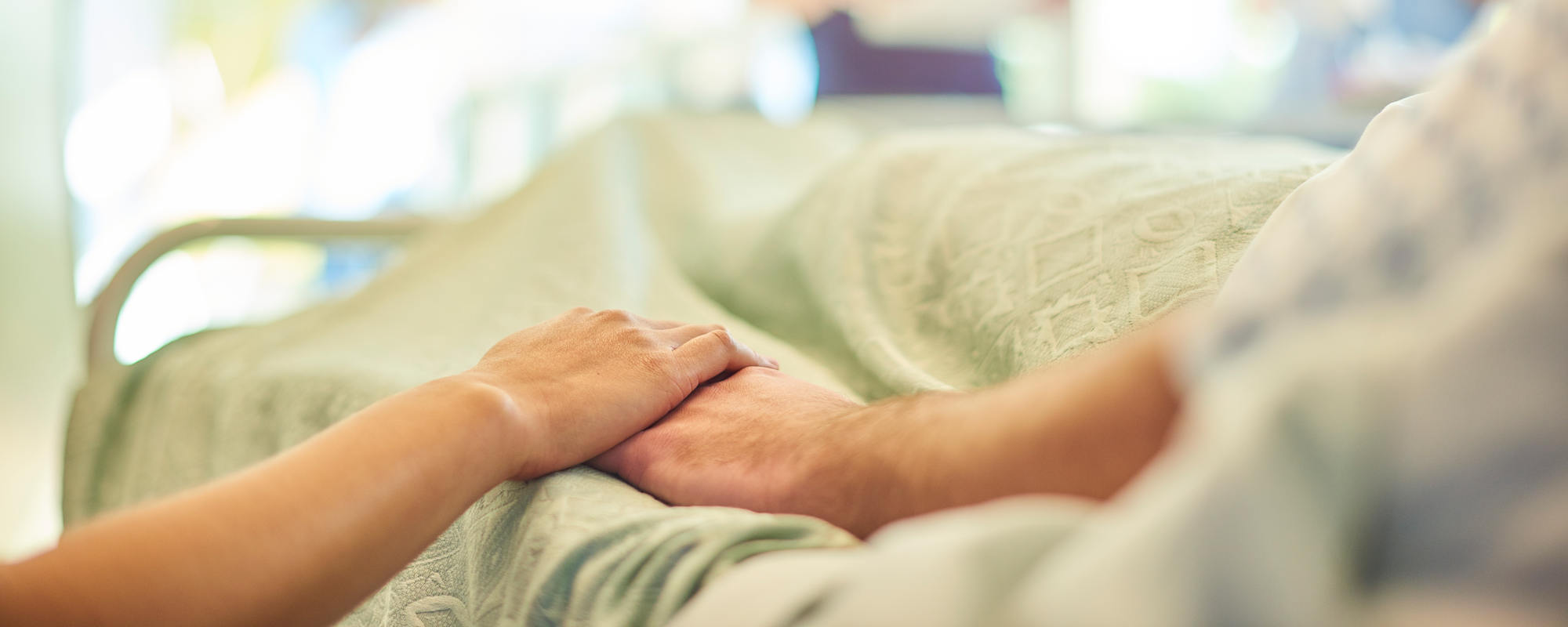 Person holding hands with someone in a hospital bed