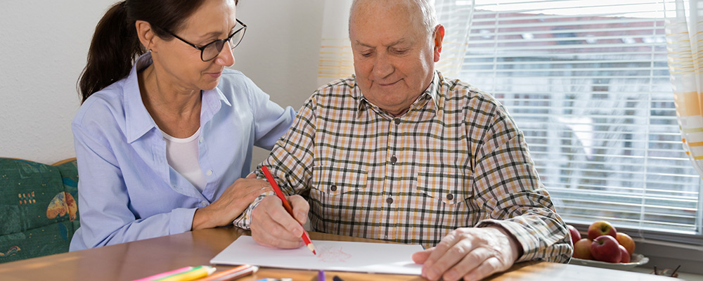 Caregiver with older adult colouring a picture.