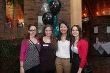 Four smiling students at send off reception.