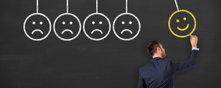 Series of sad faces on chalkboard, with a man drawing a happy face