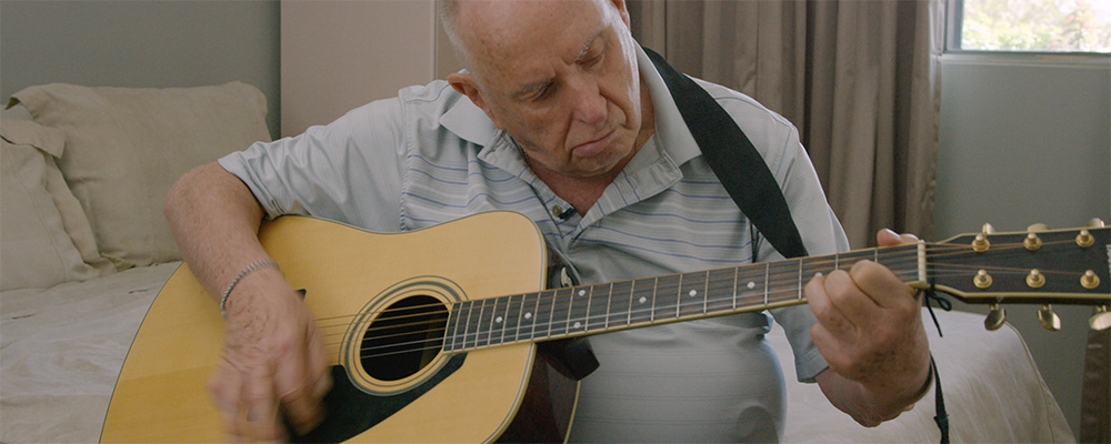 Older gentleman plays guitar.