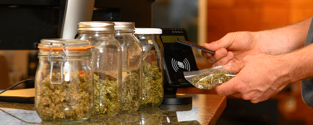 Person going to pay for a bag cannabis using credit card.
