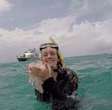 Meghan snorkeling in the sea holding jelly fish