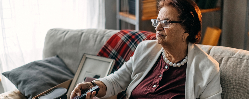 Older woman sits on couch using television remote.