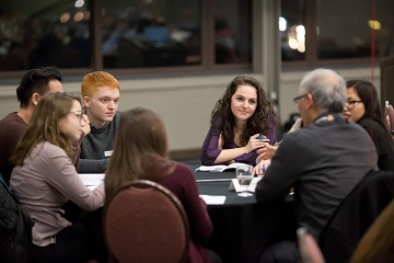 Alumnus chatting with students at career speed networking night.